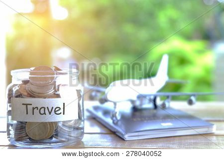 Travel budget concept. Travel money savings concept. Collecting money in moneybox for travel. Money jar with coins, aircraft, and passport poster