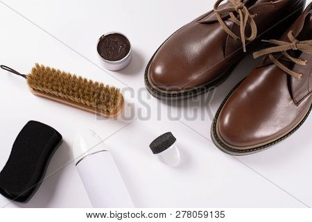 Footwear Concepts and Ideas. Care for leather shoes. Brown male shoes, Cleaning accessories, brush, cream and spray on white background. poster