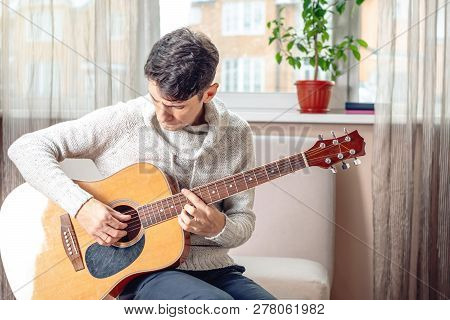 Young Attractive Male Musician Sitting On A Chair Playing Acoustic Guitar In Room. Concept Of Music