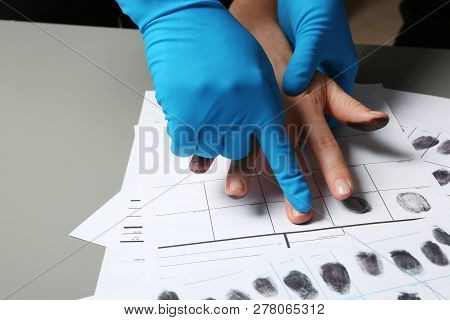 Investigator Taking Fingerprints Of Suspect On Table, Closeup