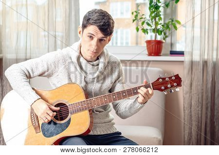 Young Attractive Male Musician Sitting On A Chair Playing Acoustic Guitar. Concept Of Music As A Hob