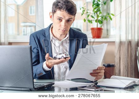 Man Agent Holding A Car Toy And Documents For Registration Of The Car. Concept Of Buying Selling And