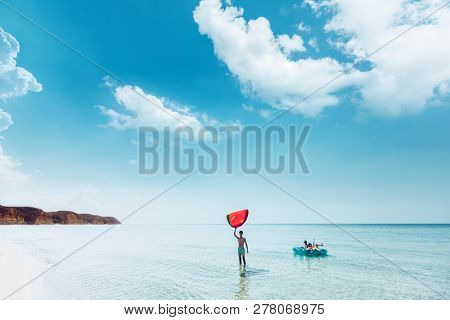 Friends on lilo chilling in the clear sea water. Girls and boy relaxing on inflatable ring on the beach. Summer vacations, idyllic scene.