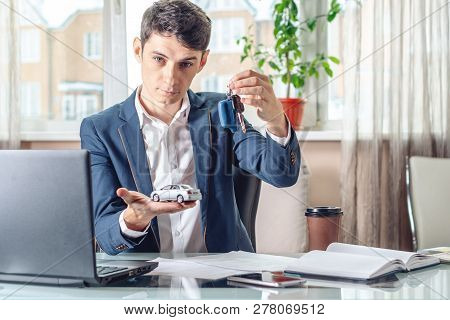 Man Agent Passes The Car Keys To The Client In The Office. Concept Of Buying Selling And Rental Of T