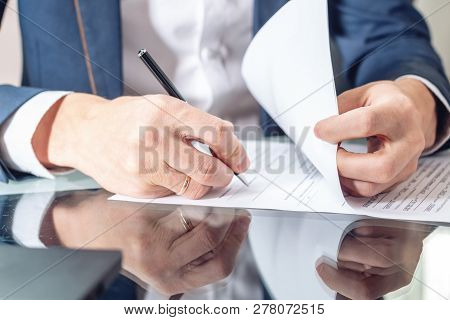 Businessman Sitting At The Table Signing Documents In The Office Close Up. Concept Of Work With Secu