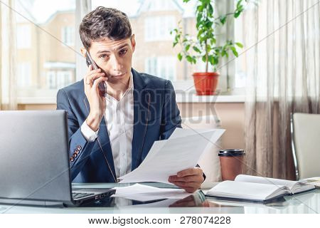 Businessman Sitting At A Work Place Examing Documents. Concept Of The Office Working With Documents