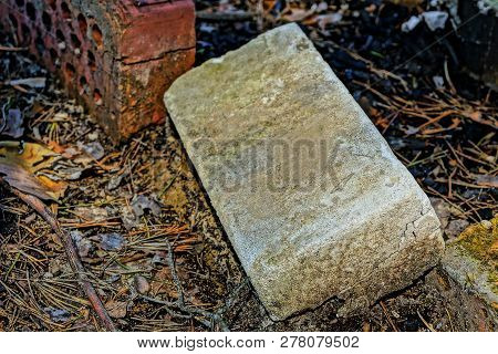 Old Gray Brick Laying On The Ground Outside