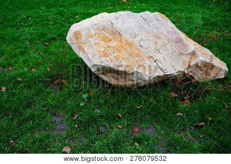 One Big Gray Brown Stone Lies On Green Grass In The Park