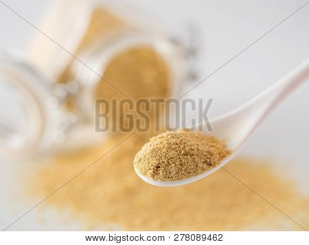 Nutritional Yeast Background. Nutritional Inactive Yeast In Small Spoon And Spilled From Glass Jar O