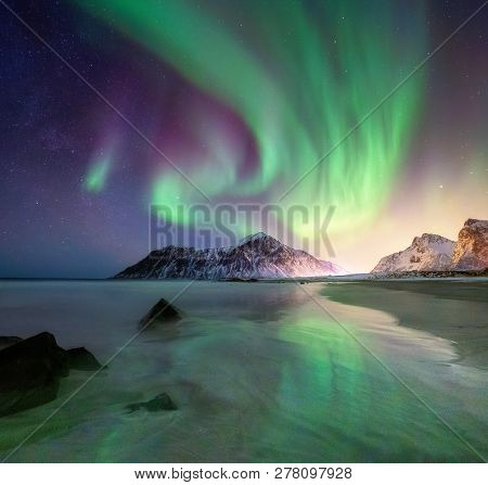 Aurora Borealis On The Lofoten Islands, Norway. Green Northern Lights Above Mountains And Beach. Nig