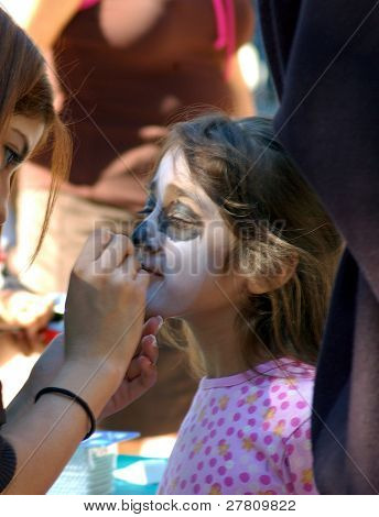 A young girl getting face painted in preperation of the closing procession of the Dia de los muertos celebrations