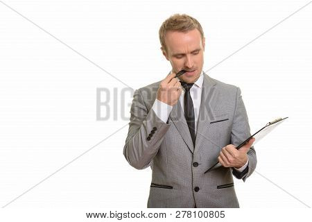 Handsome Caucasian Businessman Thinking While Biting Pen And Rea