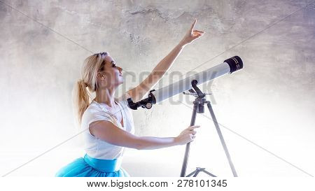 Young Woman Dreams Of The Future, Concept. Girl In The Sky With Clouds Looks Up And Uses A Telescope