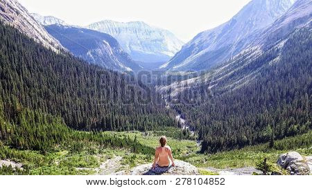 A Women Sitting Naked In The Padmasana Or Lotus Position, Meditating While Overlooking A Secluded Va