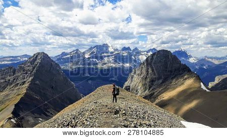 A female hiker backcountry hiking through the remote, secluded, and beautiful rocky mountains in Kananaskis, Alberta, Canada.  This hike is along the Northover Ridge with an increible ridge walk, amazing valleys, rivers, snow melts, and forests.  Truly am