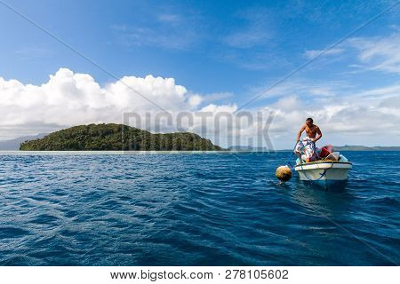 Pohnpei, Micronesia - Dec 27,2011: A Local Micronesian In A Boat Man Pulls A Buoy Out Of The Water W