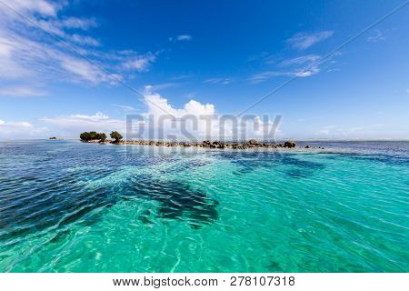 Azure Turquoise Blue Lagoon With Corals With A Small Uninhabited Reef Island Motu Full Of Dangerous
