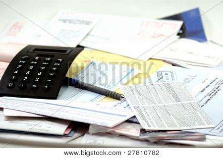 Calculator, legal pad and receipt book, paycheck and lots and lots of bills