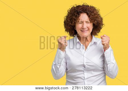 Beautiful middle ager senior businees woman over isolated background excited for success with arms raised celebrating victory smiling. Winner concept.