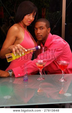 African American couple in a martini bar.Woman pouring a drink