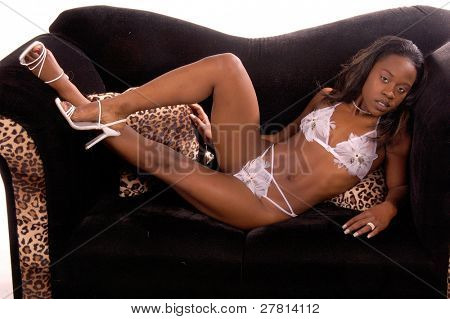 Sexy African American woman in white feathered lingerie on a black couch with leopard trim