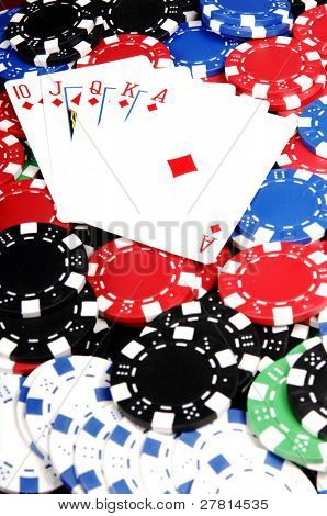 One of the highest hands in poker a Diamonds Royal Flush on a bed of poker chips