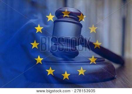 European Union Flag With Wooden Gavel In Close-up Full Frame Background Concept, Symbolising Legal V