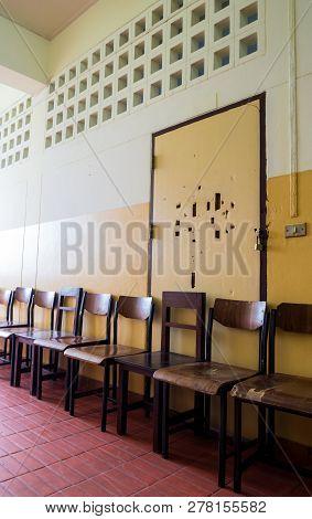 Unused Student Chair In Front Of The Broken Door Of An Old Classroom
