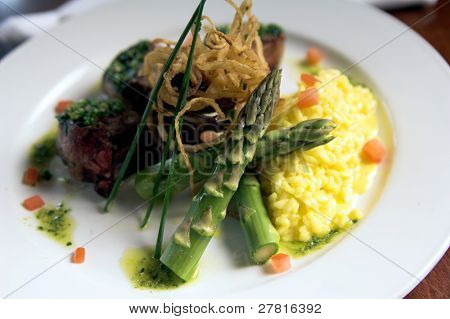 Italian dish made of braised lamb chops with rice and grilled asparagus