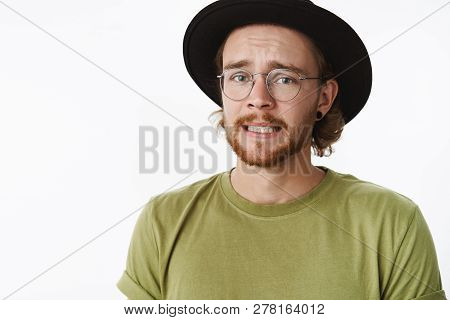 Yikes, I Am In Trouble. Portrait Of Worried Sad Cute Guy With Beard In Glasses And Hat Frowning Clen