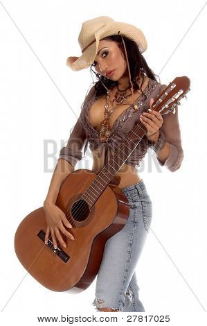 Super sexy rodeo cowgirl in torn jeans, boots and cowboy hat with a nylon string acoustic guitar