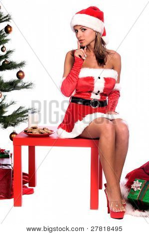 Sexy Ms. Santa Claus sitting by the Christmas tree with milk and cookies
