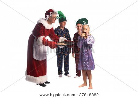 Mrs Santa Claus passing out a plate full of Christmas cookies to a group of children in pajamas and elf hats