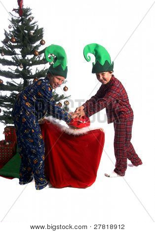 Two young boy elves in Pj's pushing a little girl elf down into Santa's bag