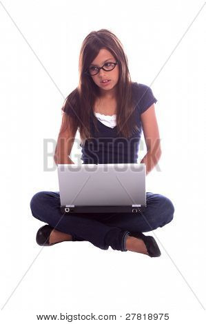 Young girl sitting cross legged on the floor doing homework on a laptop computer