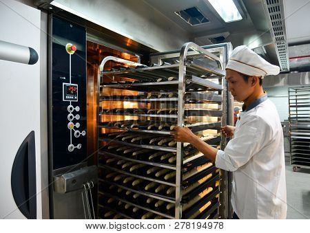 Saigon, Vietnam - Jan 9, 2018. A Man Working With Racks Of Freshly Baked Bread At The Factory In Sai