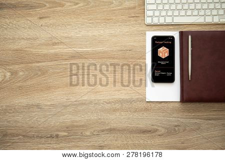 Phone With App Tracking Delivery Package On The Screen On Wooden Table With Notebook And Keyboard