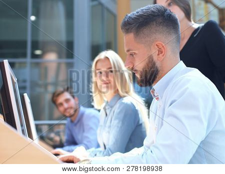 Group Of Young People In Casual Wear Sitting At The Office Desk And Discussing Something While Looki