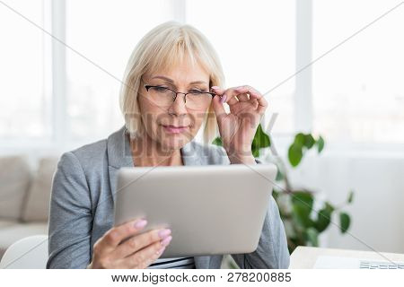 Senior Woman With Eyeglasses Browsing On Digital Tablet, Working At Home