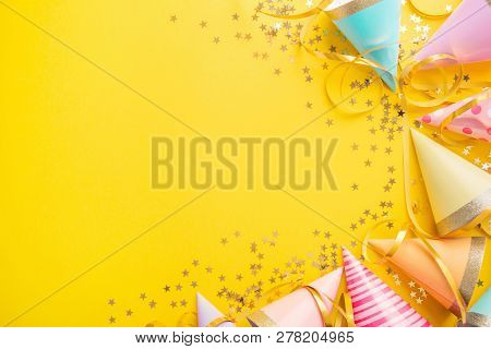 Colorful Happy Birthday Or Party Background Flat Lay Wtih Birthday Hats, Confetti And Ribbons On Yel