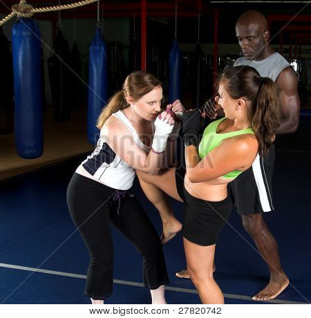 Young female MMA fighters working on knee kicks with their personal trainer in the gym