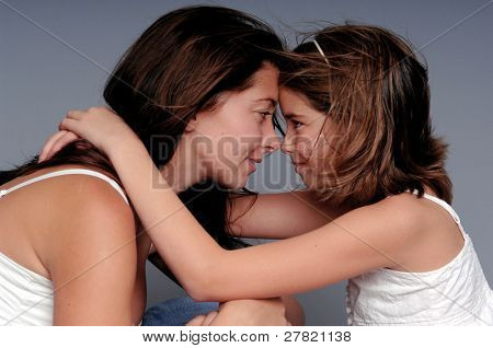A young mother shares an intimate moment with her adolescent daughter.