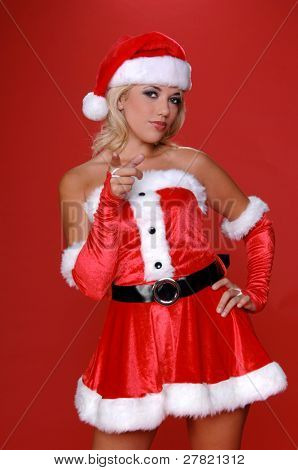 Sexy blond Mrs Santa in a red velvet suit points her finger at the viewer. Half body image