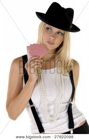 Young blonde woman in suspenders and a fedora playing her cards close to her chest