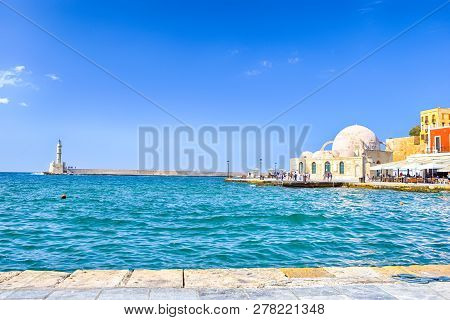 Travel Ideas. Chania Old Port And Venetian Harbor With Ancient Lighthouse On Background.horizontal I