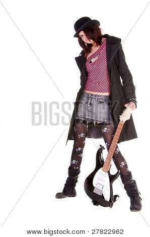Beautiful and hip scene girl with red and black hair in a pink striped off the shoulder top, pirate sleeves and a felt bowler playing an electric guitar