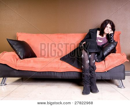 Beautiful and hip scene girl with red and black hair in a pink striped off the shoulder top, pirate sleeves and a felt bowler relaxing on a couch