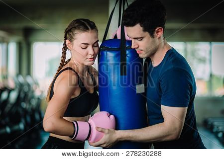 Fit Beautiful Woman Boxer Hitting A Huge Punching Bag Exercise Class In A Gym. Boxer Woman Making Di