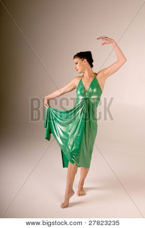Female dancer in a metallic green dress performing on stage. Dress is made of a very shiny, metallic and grainy material.