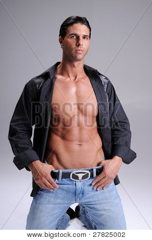 Muscular young man standing in jeans and an unbuttoned black long sleeve dress shirt neck tee shirt